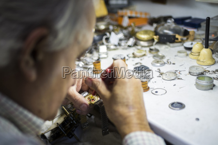 watchmaker in foreground while working with