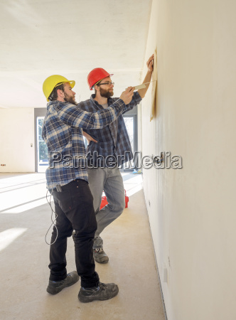 two craftsmen discussing plan in construction