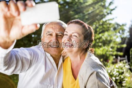 happy elderly couple taking a selfie
