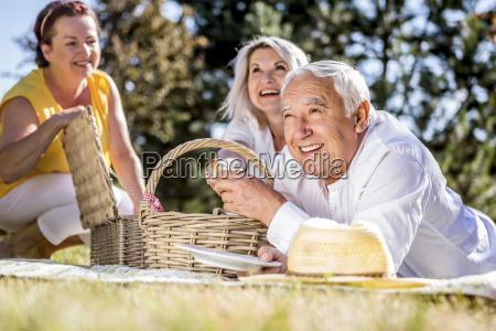 happy elderly friends having a picnic