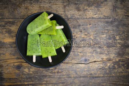 bowl of homemade kiwi ice lollies