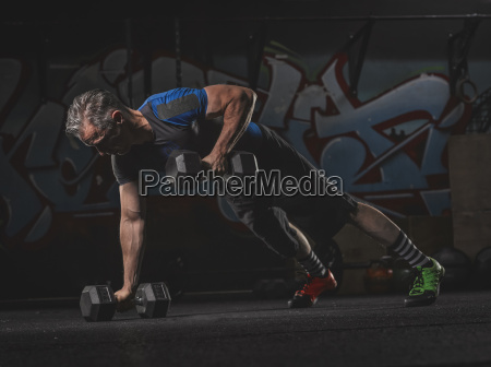 mature crossfit athlete exercising with dumbbells