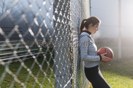 young woman with basketball leaning against
