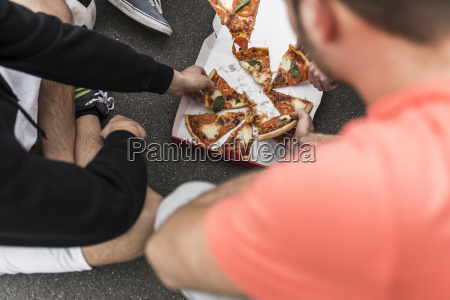 young men eating pizza