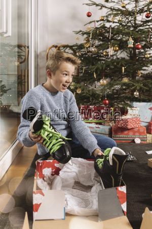 little boy unwrapping a christmas gift