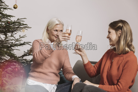 senior woman and younger woman clinking
