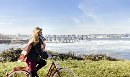 spain gijon smiling young woman riding