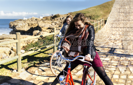 two happy young women riding bicycle