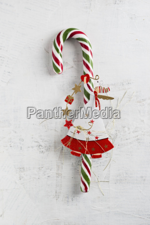 candy cane with angel figurine on