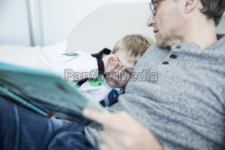 father reading book to tired boy