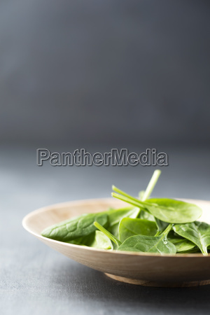wooden bowl of spinach leaves close
