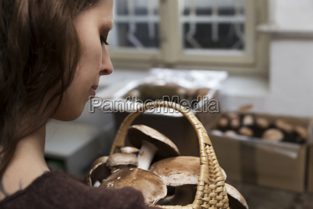 woman looking at basket with crimini