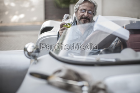senior man in sports car looking