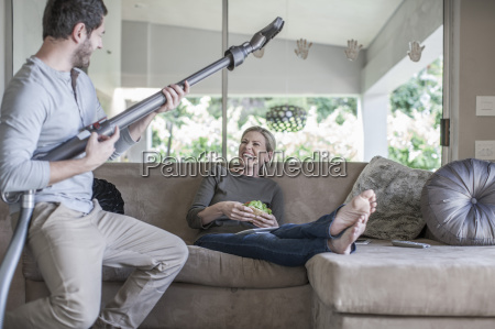 woman on couch and man pretending