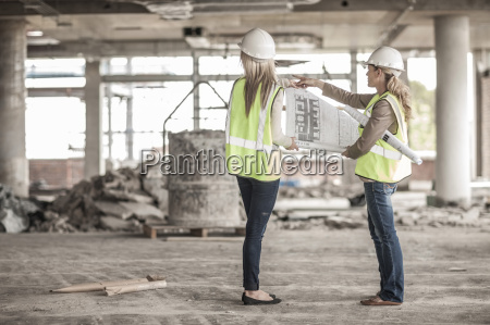 two women in protective workwear discussing