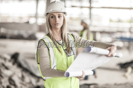 woman in protective workwear holding building
