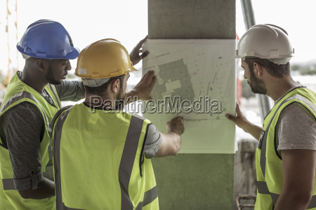 construction workers discussing building plan in