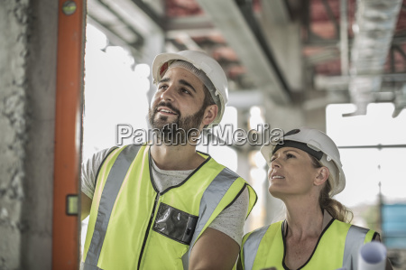 woman with construction worker using water