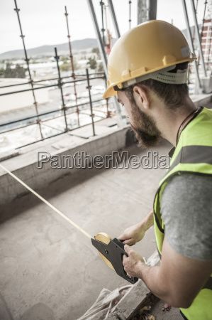 construction worker using tape measure in