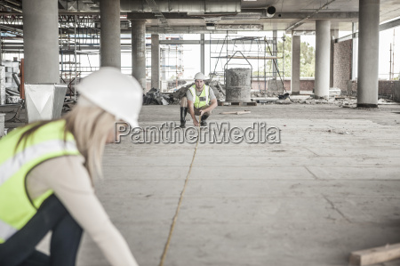 construction worker and woman using tape