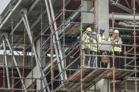 construction workers and architects with building