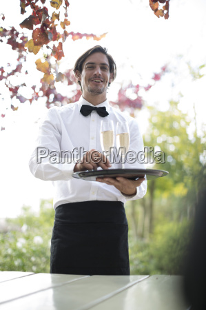 waiter outdoors serving champagne