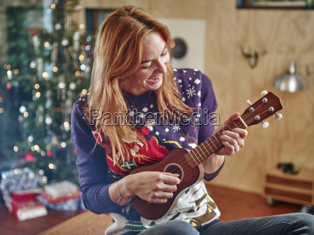 blond woman playing ukulele in front