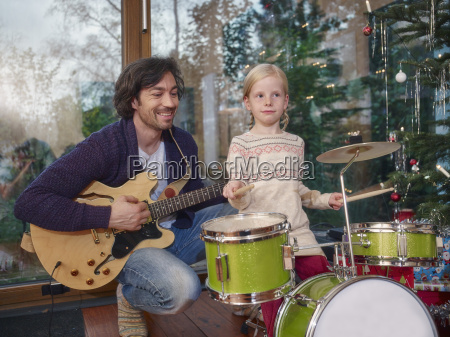 father and daughter playing music on