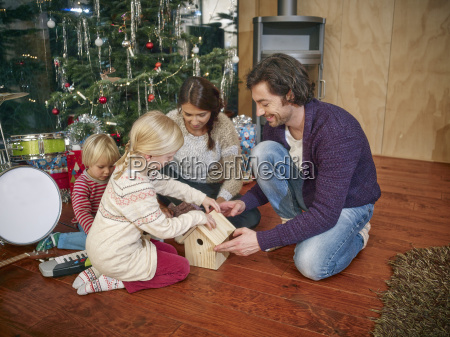 parents playing with daughters on christmas