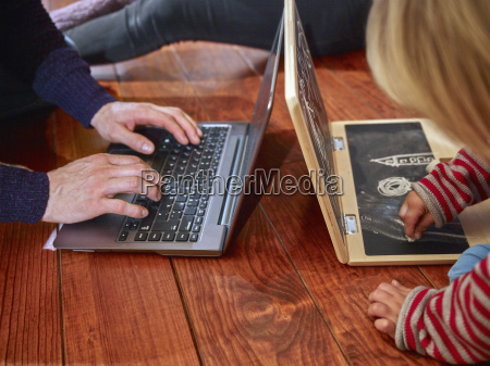 father using laptop sitting on floor