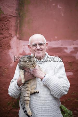 portrait of senior man holding tabby
