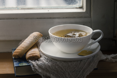 chamomile tea and biscuits on windowbench
