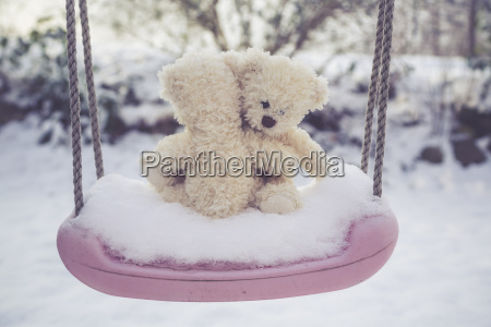 two clasping teddy bears on snow