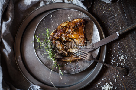 baked rabbit legs on plate thyme