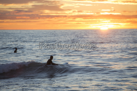 two surfers at sunrise