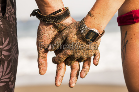 close up of couple holding sandy