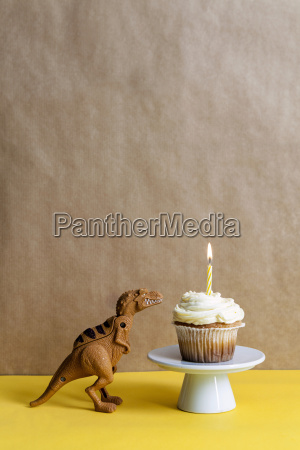 toy dinosaur and cup cake with