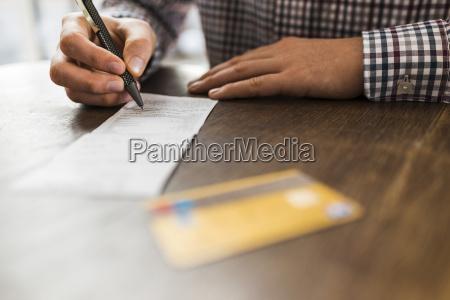close up of man signing bill