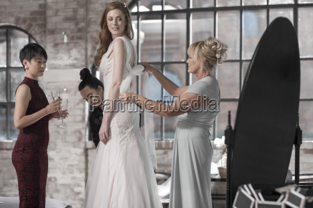 mother and bridesmaid helping bride putting