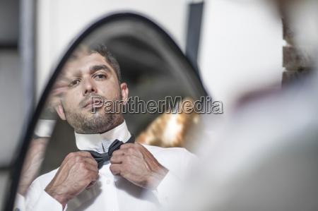 man looking in mirror adjusting bowtie