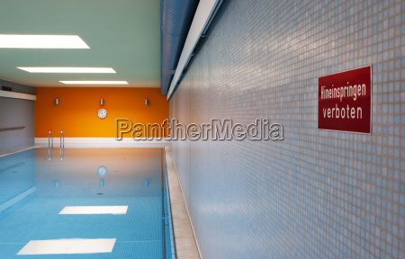 empty indoor swimming pool with sign