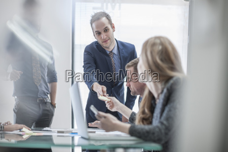 businessman handing over note to colleague