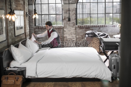 housekeeper in hotel room making the
