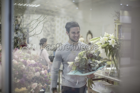 smiling young man with bunch of