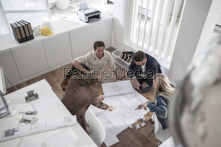 four people in office working together