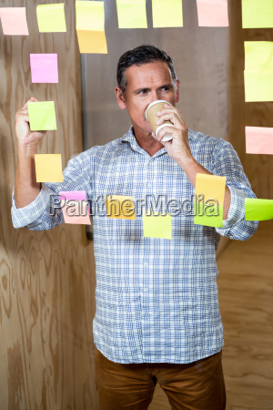 man writing on sticky notes while