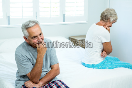 sad senior man and woman sitting