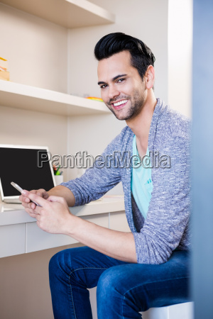 happy man using smartphone and laptop