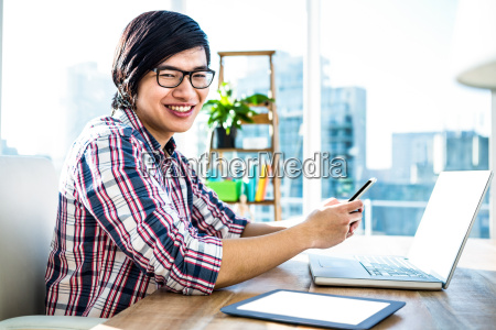 smiling hipster businessman using smartphone