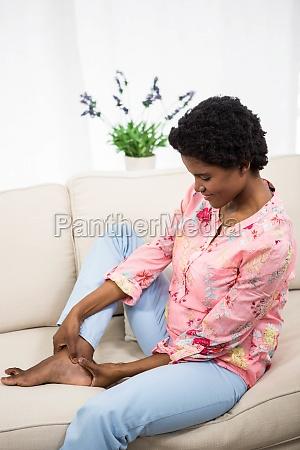 pregnant woman touching feet